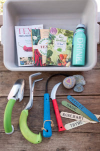 A sturdy plastic bin, gardening books, ergonomic hand tools, metal plant stakes and other tools